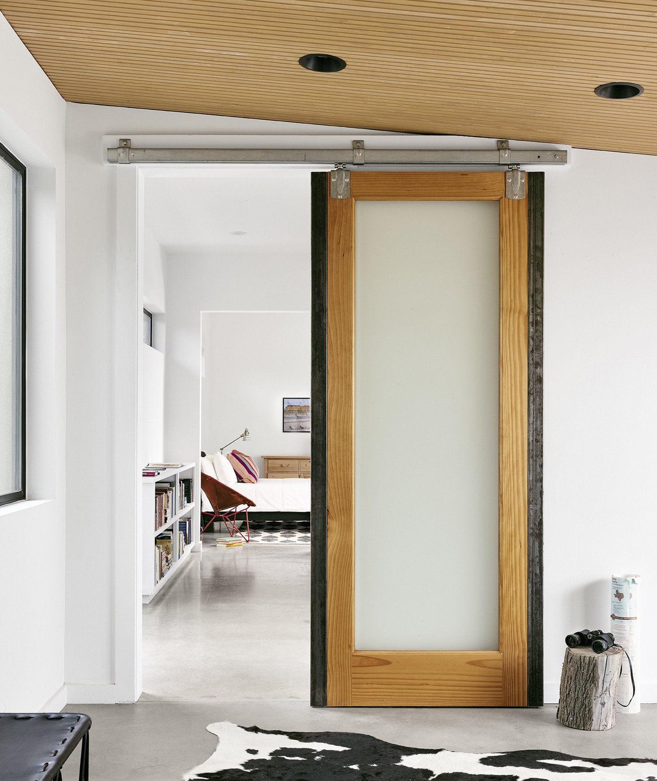 Pops of color and warm materials, like the sliding wooden barn doors from Simpson, provide a cozy contrast to the polished concrete floors throughout. Tagged: Hallway and Concrete Floor.  Photo 2 of 6 in The Long Way Home