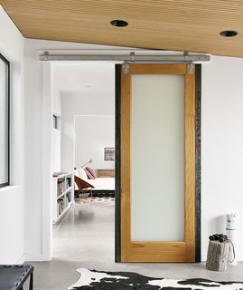 The Long Way Home - Photo 2 of 6 - Pops of color and warm materials, like the sliding wooden barn doors from Simpson, provide a cozy contrast to the polished concrete floors throughout.