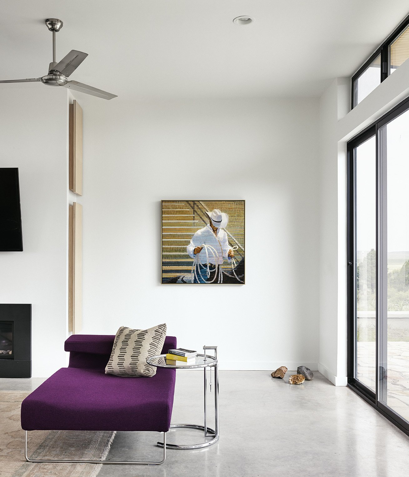 Flanked by sliding glass doors, the living room includes a Lowseat chaise longue by Patricia Urquiola for Moroso, paired with an E1027 side table by Eileen Gray. Tagged: Living Room, Bench, End Tables, Concrete Floor, Sofa, Rug Floor, and Recessed Lighting.  Photo 5 of 6 in The Long Way Home