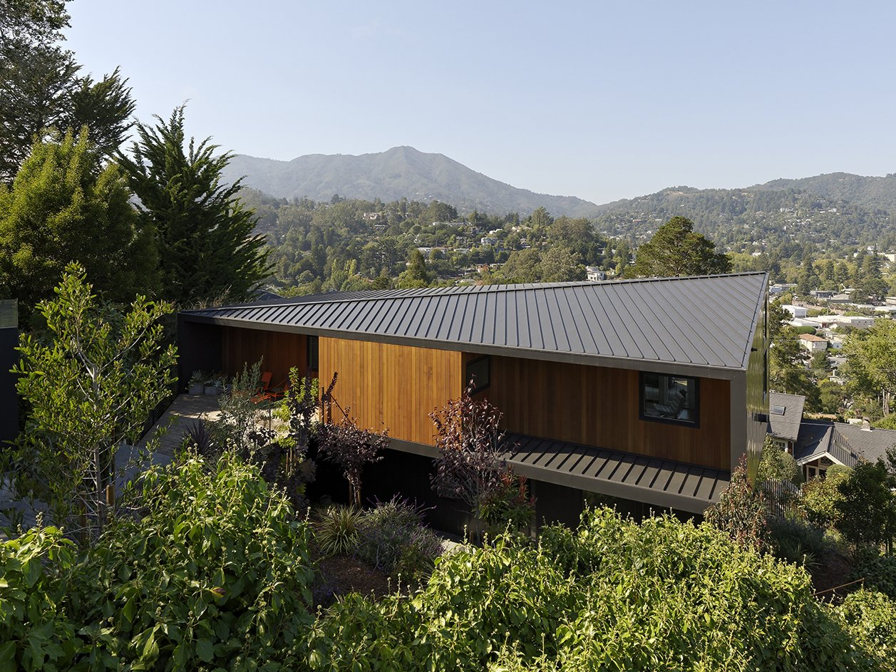 """At the Mill Valley home designed by architect Chris Deam for residents Jack and Ellen Corrigan, the view begins from the top. Sun studies of the steeply sloped site informed the choice for a standing-seam metal, diagonal ridge roof, which Chris refers to as the home's """"fifth facade"""". Tagged: Outdoor.  Photo 1 of 15 in Moving Mountains"""