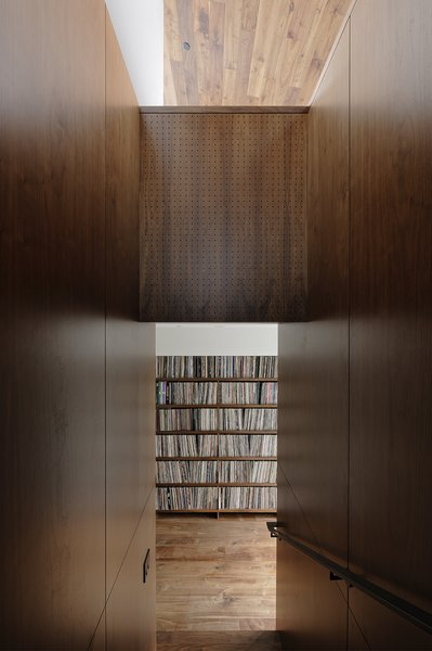 The adjacent volume houses the galley kitchen; the Ball clock is by George Nelson Associates.A portion of Jack's massive collection of more than 10,000 records is displayed in a low-slung walnut shelving unit built along the upstairs stairwell entry.