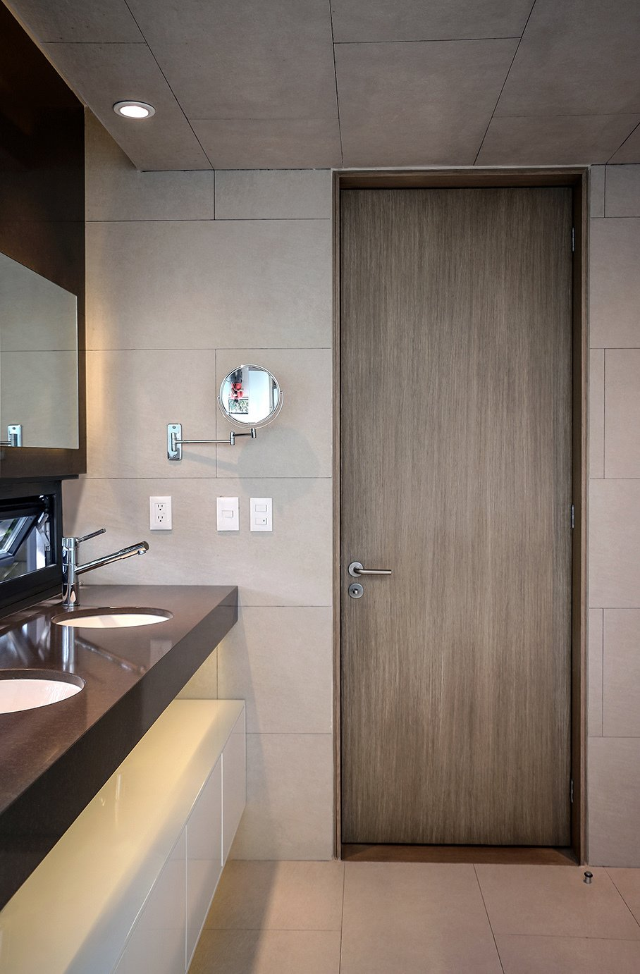 The door is made of MDF panels attached  to a wood frame and topped with an ash veneer. The tiles are from Spanish brand Vives. Tagged: Bath Room, Engineered Quartz Counter, Recessed Lighting, Cement Tile Floor, Drop In Sink, and Stone Tile Wall.  Photo 8 of 13 in Retired Couple Build Modern in Mexico City