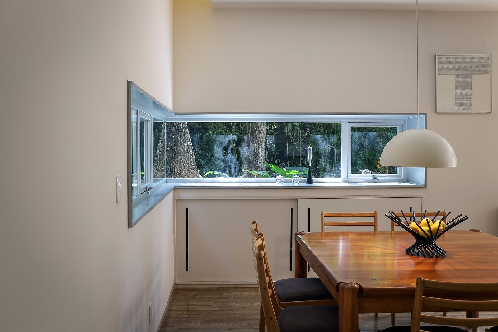 The dining area's aluminum window frame was custom cut onsite to wrap around  a corner. Tagged: Dining Room, Chair, Table, Pendant Lighting, and Medium Hardwood Floor.  Photo 10 of 13 in Retired Couple Build Modern in Mexico City