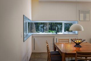 Retired Couple Build Modern in Mexico City - Photo 9 of 12 - The dining area's aluminum window frame was custom cut onsite to wrap around <br>a corner.