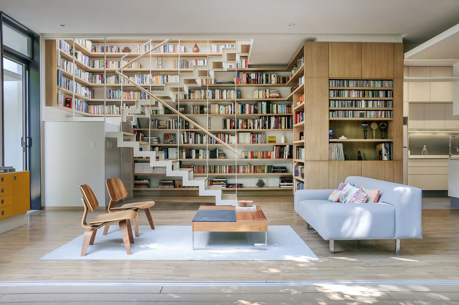 A pair of Molded Plywood lounge chairs by Charles and Ray Eames for Herman Miller sit opposite a BoConcept coffee table and a sofa of Paul's design. For his father's book collection, Paul created a library around the double-height staircase. Tagged: Chair, Sofa, Light Hardwood Floor, Shelves Storage Type, Staircase, Wood Tread, and Wood Railing.  Photo 12 of 13 in Retired Couple Build Modern in Mexico City