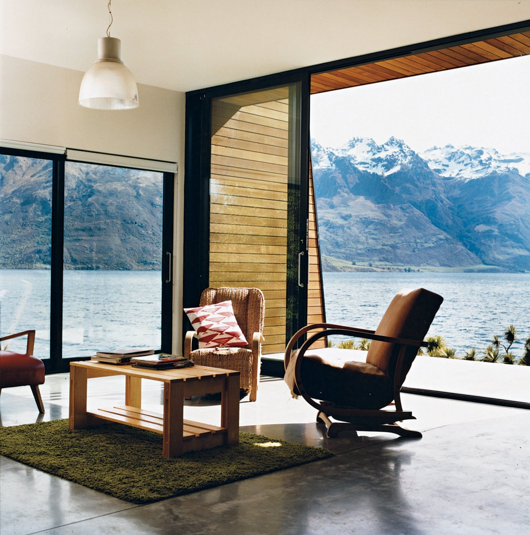 The main living area. The home is flanked on the east by a precipitous mountain range named The Remarkables. In summer, the weather gets hot enough for the family to go swimming and boating. Tagged: Living Room, Chair, Concrete Floor, Coffee Tables, and Pendant Lighting.  Drift Bay House by Dwell
