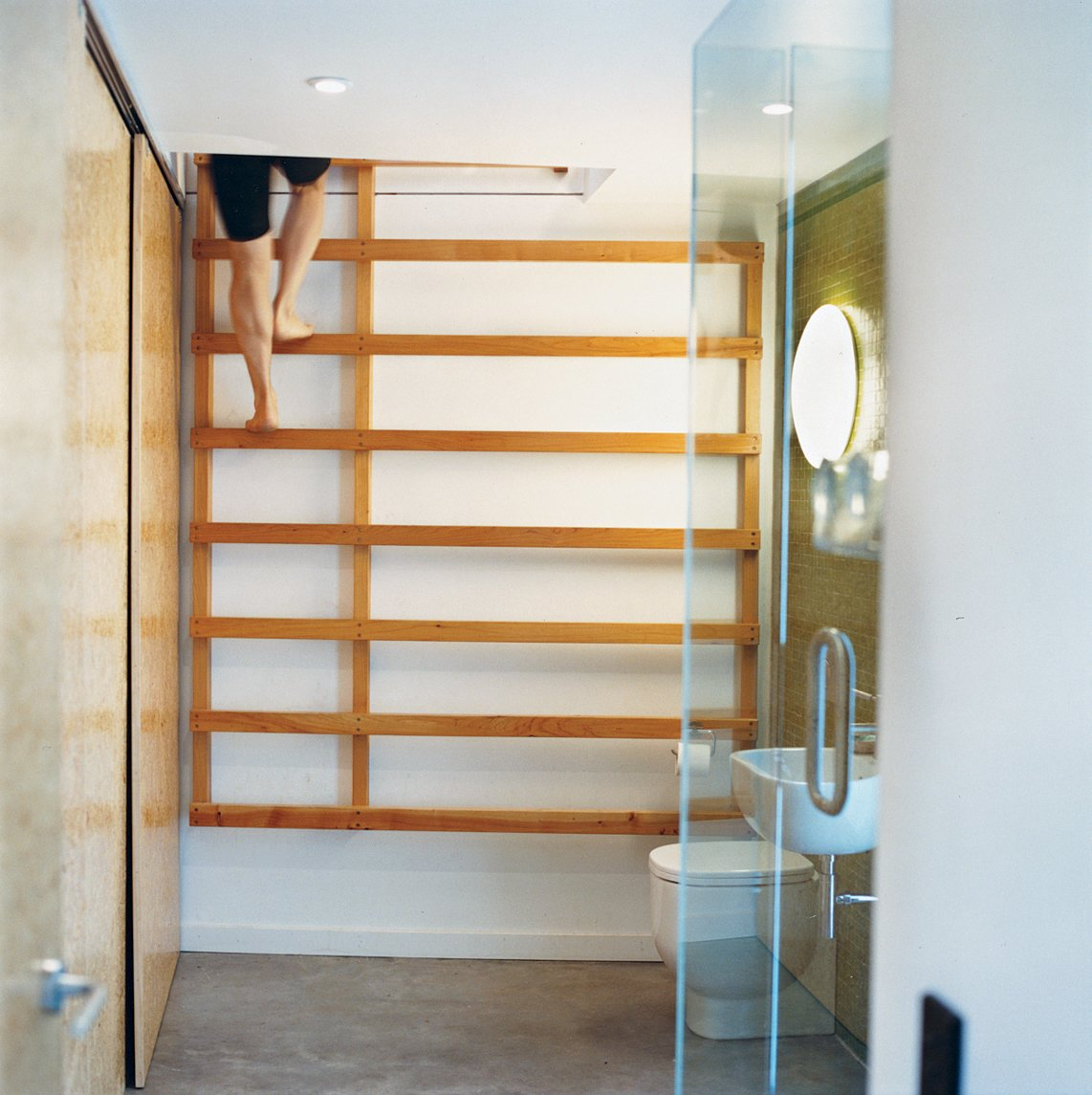 One bathroom features a ladder that leads up to a yoga studio.  Drift Bay House by Dwell