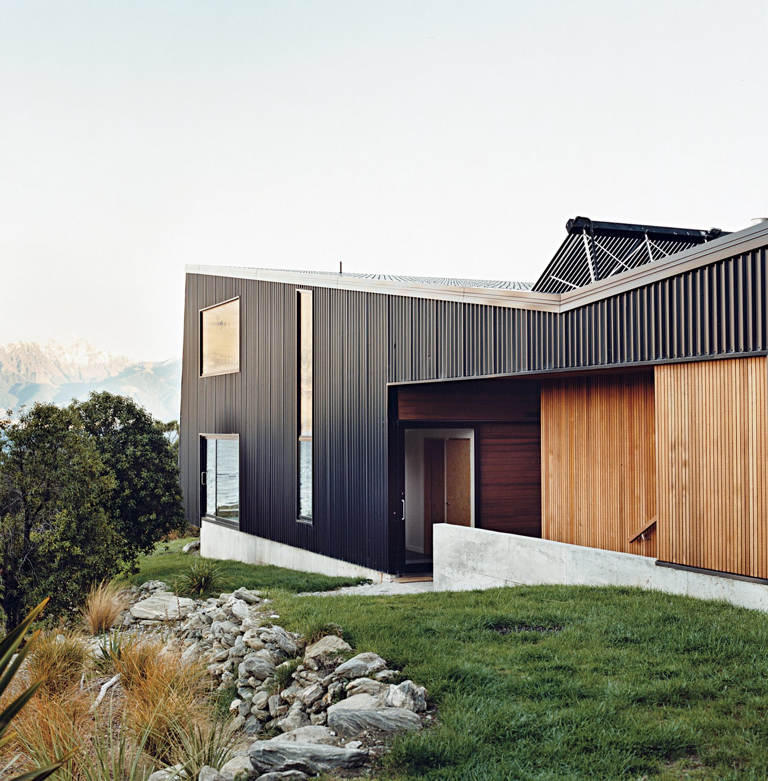 "The home is mostly clad in black trapezoidal-profile steel, with cedar boards lining what the owners call the ""human spaces""—external passages between buildings. A solar hot water system perches on the roof. Tagged: Exterior, Metal Siding Material, House, Metal Roof Material, and Wood Siding Material.  Drift Bay House by Dwell"