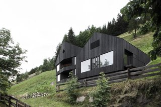 13 Epic Alpine Retreats We're Swooning Over - Photo 13 of 13 - Nestled in the Dolomite mountains of northeastern Italy, La Pedevilla is a modern cousin to the traditional farm homes dotting the picturesque hamlet of Pliscia. Its larch wood cladding, painted black, stands both in contrast to the surrounding greenery and in conversation with the distant Alps, a fitting metaphor for a structure that straddles the divide between the old world and the new. Only local materials were used to build the chalet, including the larch wood cladding of the exterior, to reinforce the connection between indoors and outdoors.