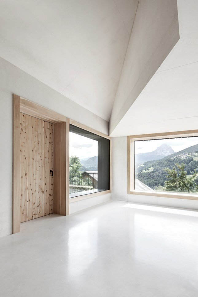 In contrast to the dark exterior, the interior is made of white concrete with aggregates of dolomite rock.