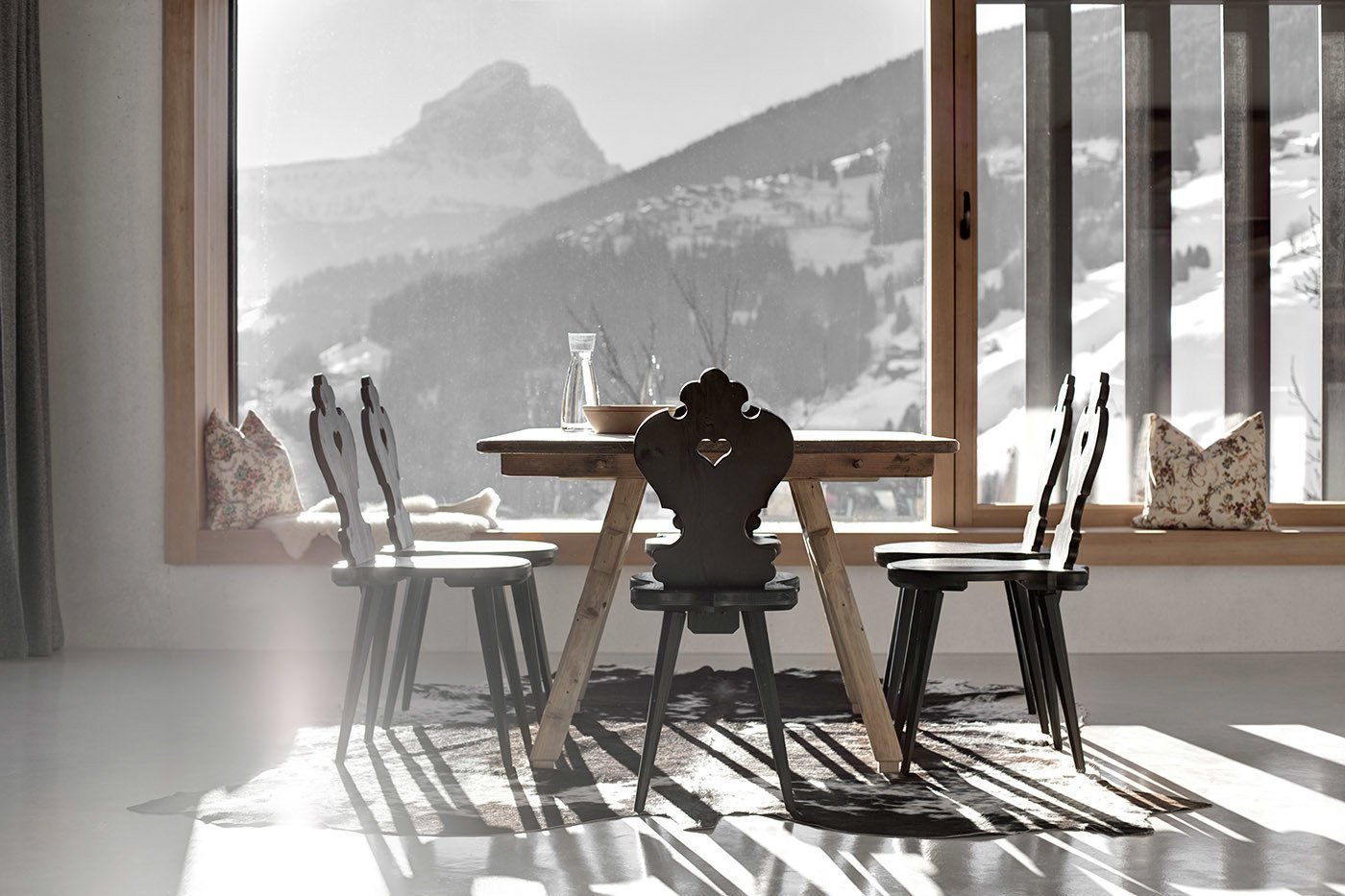 The kitchen and dining room enjoy panoramic mountain views. Local pine was hand-hewn for the flooring, windows, doors, and furniture throughout the residence. Tagged: Dining Room, Table, Chair, and Concrete Floor.  La Pedevilla by Dwell