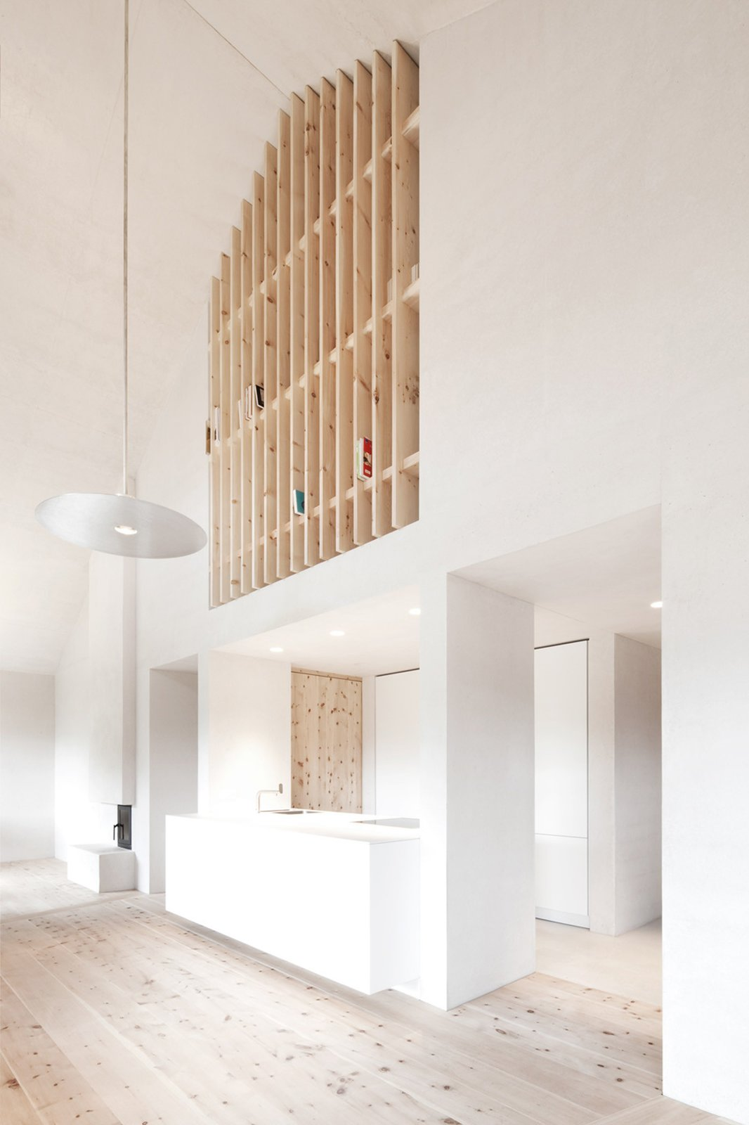 Upstairs, a wooden slatted wall doubles as a bookshelf.  La Pedevilla by Dwell