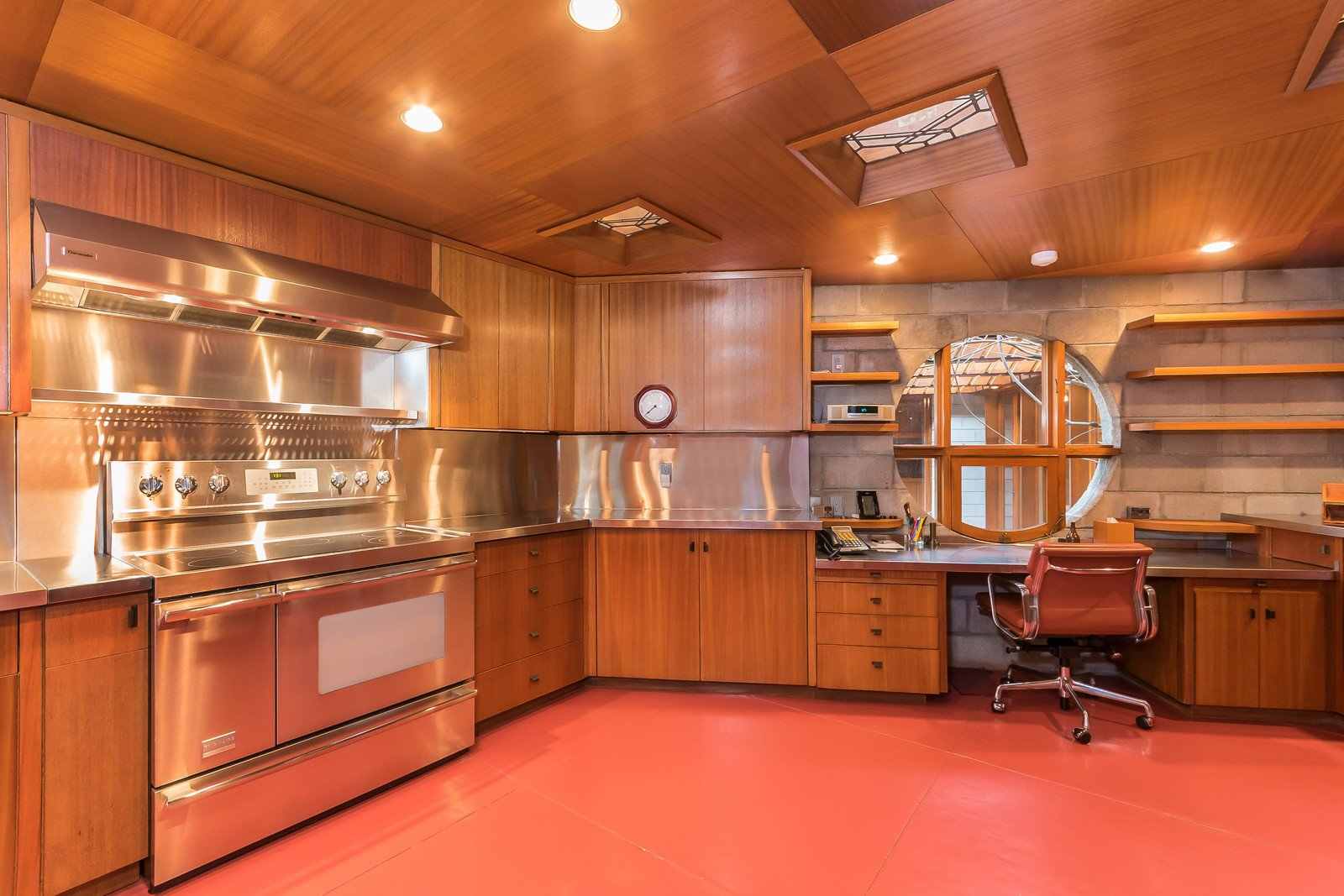 Though the appliances have been updated, the rest of the kitchen is original, including the cabinets, piano hinges, and the painted glass windows on the ceiling.