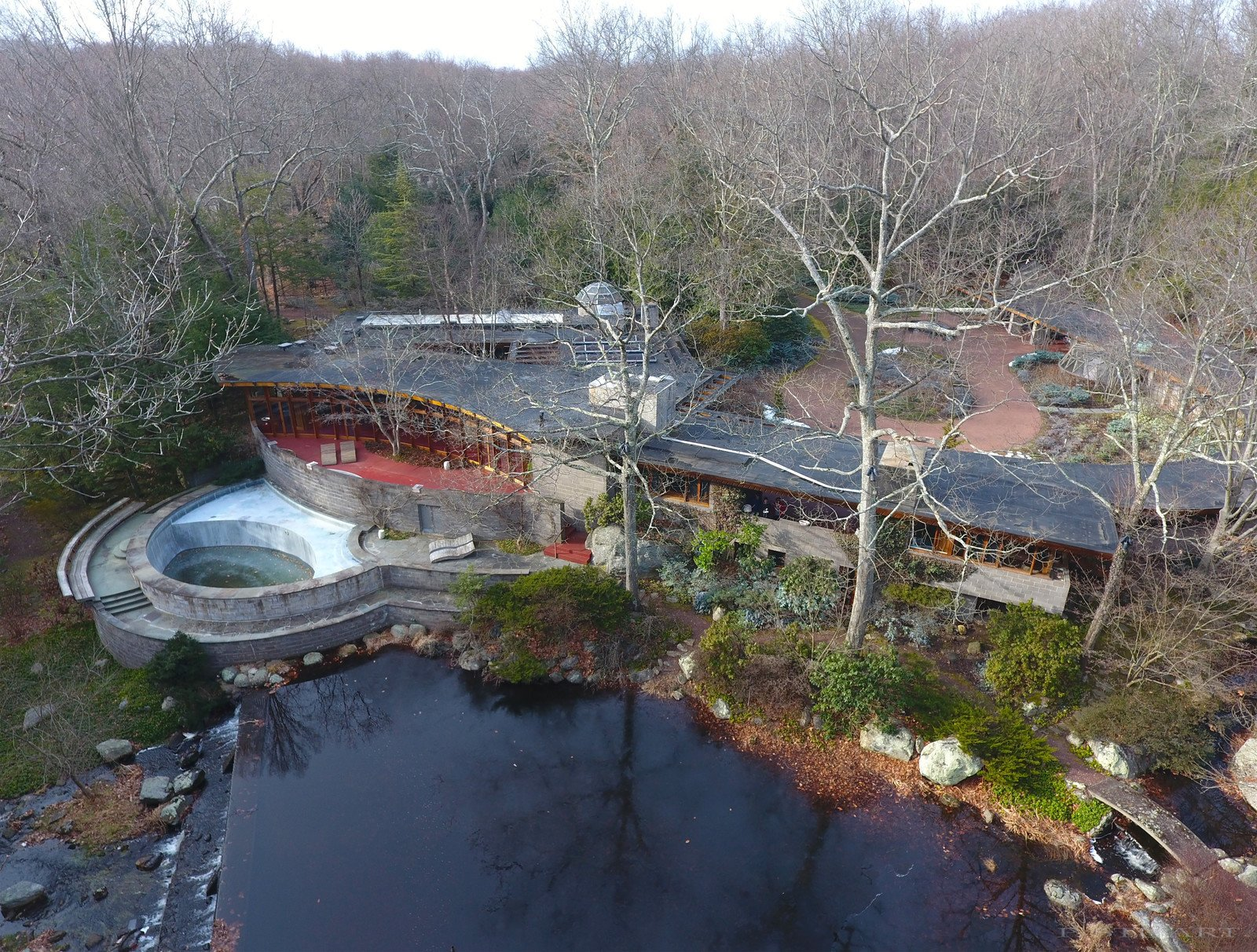 An overhead drone view shows the 15-acre property that also hosts a heated pool, river, tennis court, barn/stable, sculpture path, and rooftop observatory. The original landscaping was designed by Frank Okamura and Charles Middeleer.