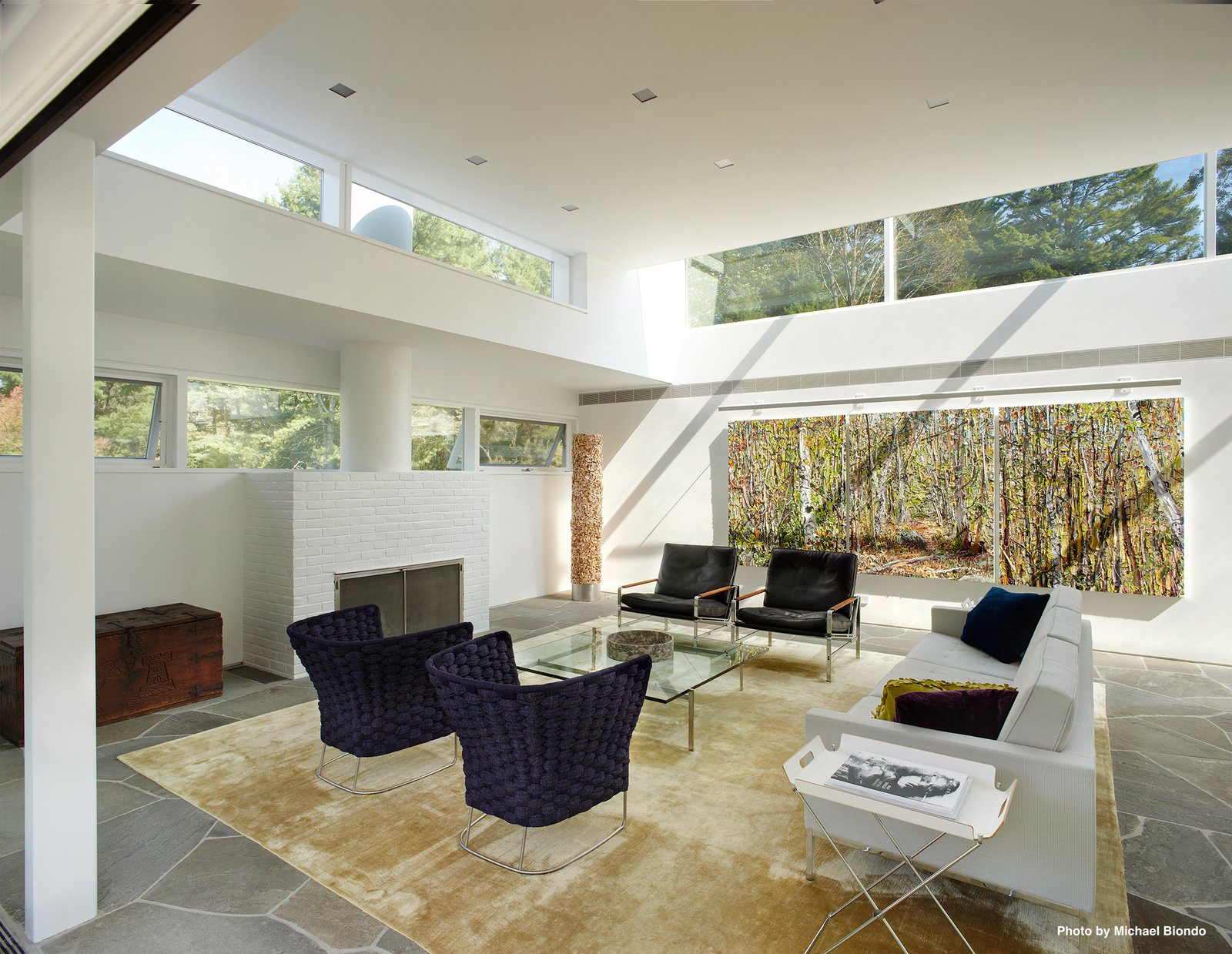 The ceiling heights were preserved throughout much of the house while skylights were placed all around the perimeter of the main structure. The living room holds an original fireplace (shown here).  Marcel Breuer's New Canaan Home by Dwell