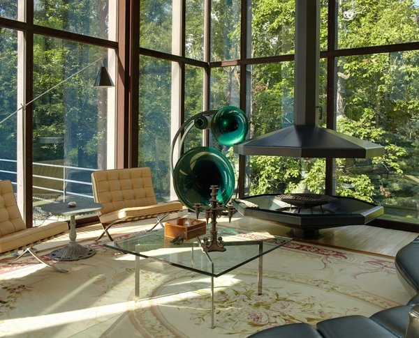 Out of the 3,544 square feet of the residence, 1,000 square feet of it comes from the pavilion. The corner of the open living room contains a suspended fireplace, oversized German speakers, and a pair of Barcelona chairs by Ludwig Mies Van Der Rohe.  Photo 5 of Wiley House modern home