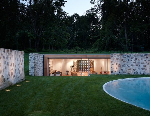 Taking a peek into the new pool house that helps enclose the area, you can see how the sloped land and the original stone walls allow it to remain surprisingly hidden from the outside.   Photo 2 of Wiley House modern home