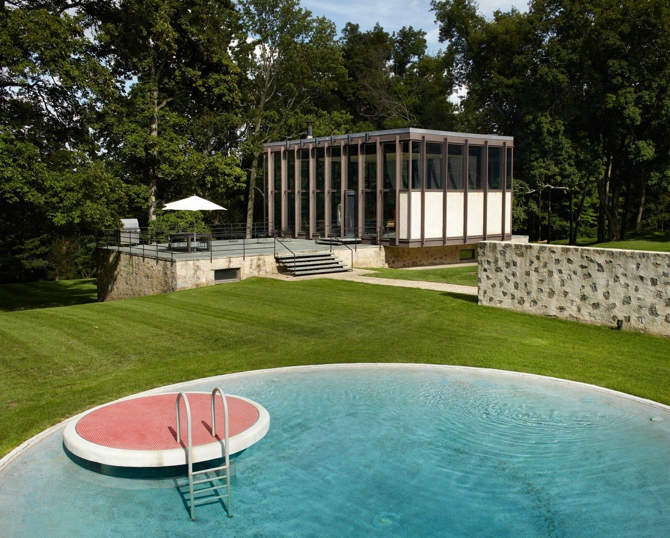The new pool house and transformed barn that were created by Roger Ferris + Partners during a recent renovation, work together to create a courtyard that borders the original swimming pool. While a very similar circular pool can be found at the Glass House, this one features a lily pad diving platform that's finished with red tile.  Wiley House by Dwell