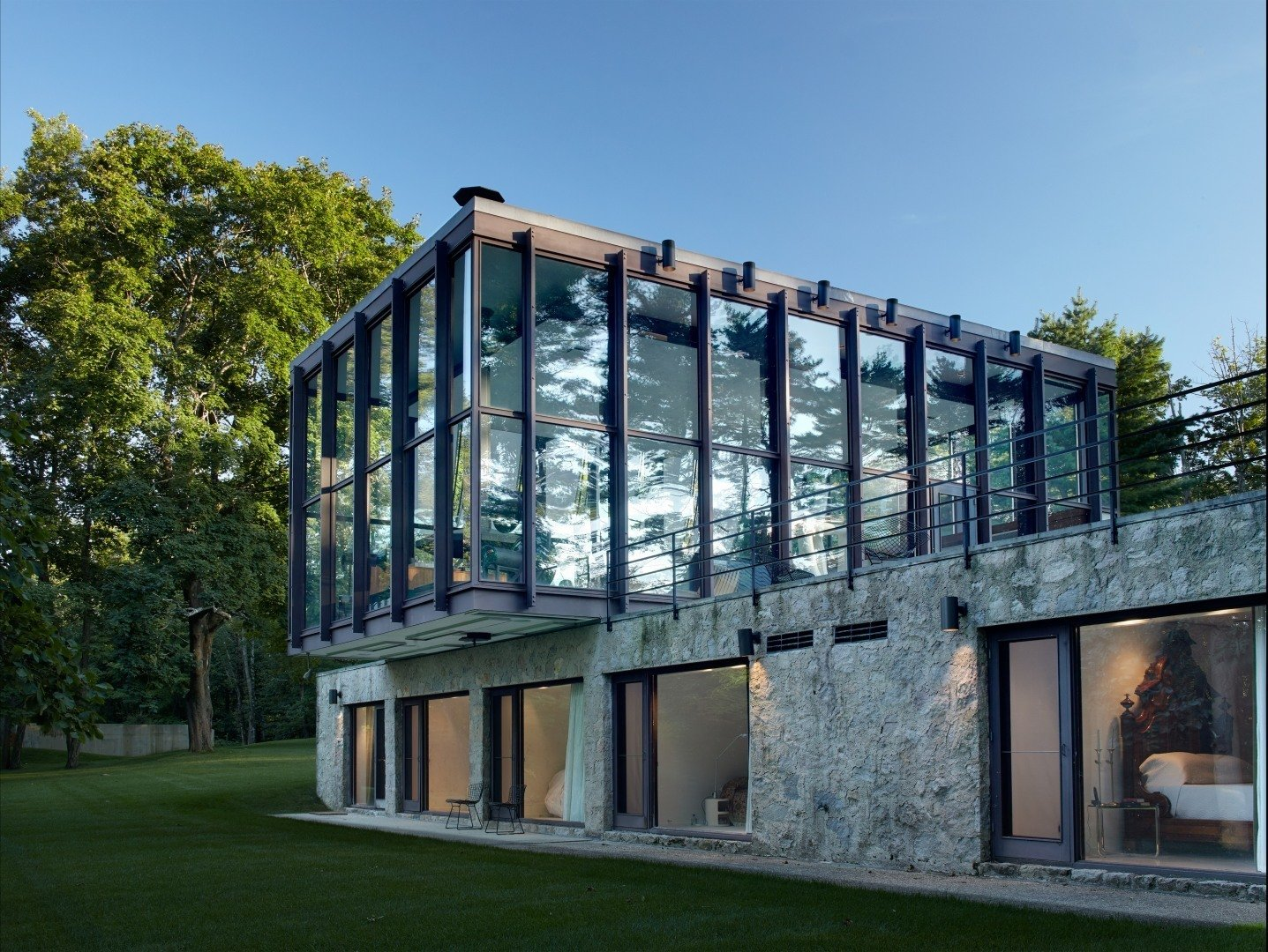 Shown here is a view of the stone and concrete structure that supports the cantilevered glass pavilion. The bottom section holds four bedrooms, bathrooms, and a sitting room. The glass and wood pavilion on top houses a combined living, dining, and kitchen space—all which is surrounded by 15-foot-tall windows.  Wiley House by Dwell