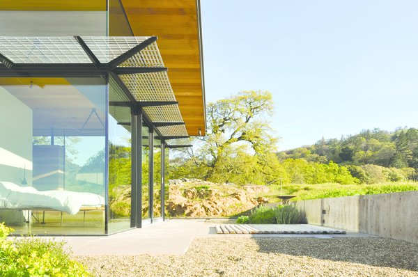 Sixteen-foot-tall glass walls, paired with seven-foot overhangs and three-foot solar screens, optimize the home's passive climate control and capture views of the  valley that unfurls across the couple's 160-acre property.