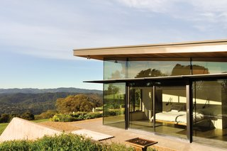 Contrasting expanses of glass and rammed earth wrap Bill Gawthrop and Diane Taylor's home in Yorkville, California. The couple's bedroom is located at one end of the house and their offices are at the other, with an open-plan kitchen, living room, and dining area in between. The bed frame is Gawthrop's own design.