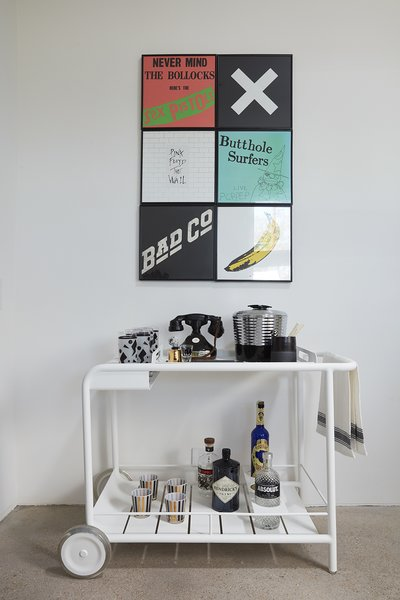 A Fermob cart holds vintage barware beneath a collection of favorite album covers.