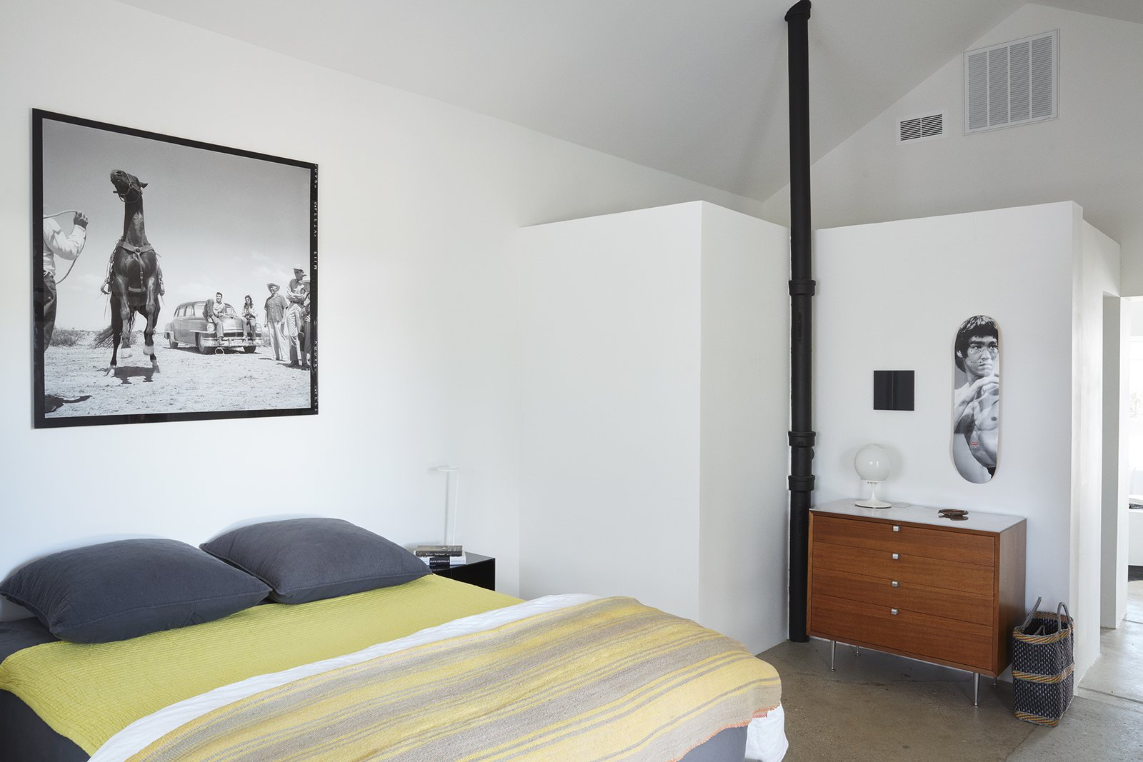 The ceiling is 15 feet high in the bedroom, where a photograph from the set of the movie Giant, which was filmed in Marfa, complements <br>a chartreuse throw from El Cosmico and a Bruce Lee Supreme skate deck from Exhibitions 2d.