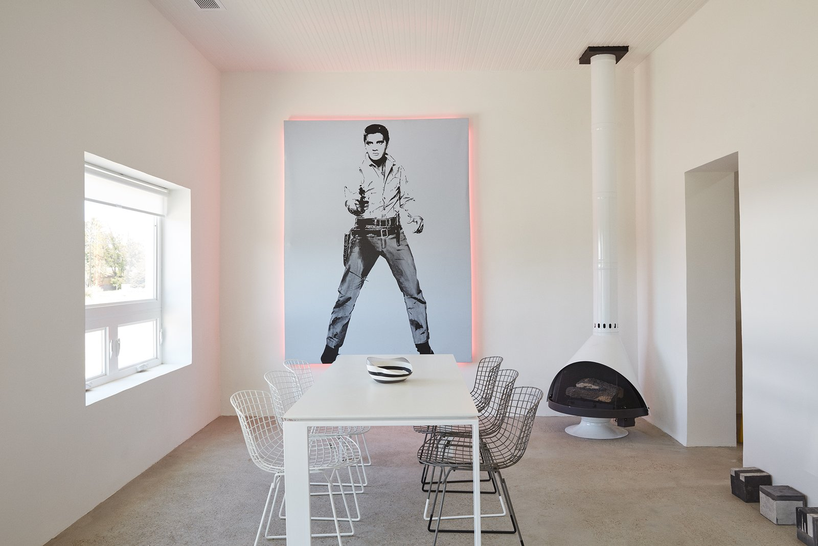 """Everything out here has been something else,"" designer Barbara Hill says of Marfa, Texas. It's certainly true of her casita, which was formerly a grocery store: The 1,200-square-foot home is filled with reworked pieces, including <br>the Elvis artwork she embellished with pink lights fabricated by the Neon Gallery in Houston and the <br>refurbished Bertoia chairs from <br>Cast + Crew. The minimal color <br>palette is echoed in the freestanding <br>Malm fireplace and the concrete floor sculptures by William Vizcarra from Wrong Marfa."