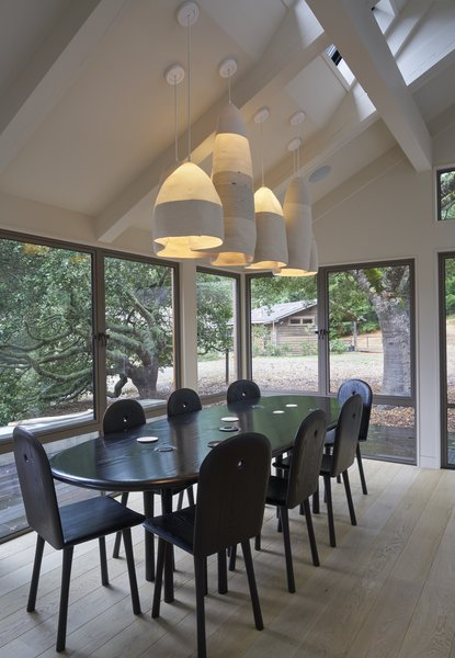 "A pendant by Doug Johnston, represented by Patrick Parrish, hangs over a custom dining table by Christopher Kurtz. ""Working with [Kurtz] was a privilege and beautiful experience,"" says the homeowner. ""He sent us a video of a stream with eddies in it, and I thought that was so appropriate: you look out at the meadow and the forest, and the lights are kind of like mountains."" The oval shape encourages everyone sitting around it to engage in one conversation. Photo 5 of Beetlebung modern home"