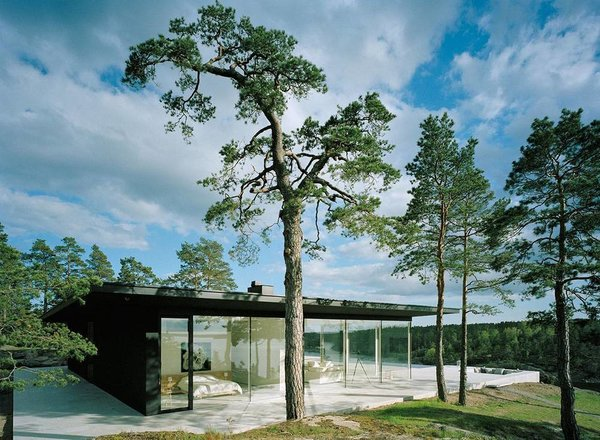 The matte black exterior and floor-to-ceiling glass of Villa Överby sit flush on limestone slabs.