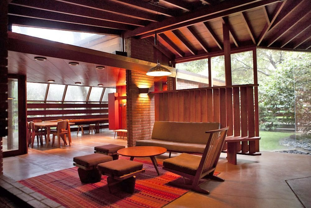 Built with redwood, glass, red brick, and concrete John Lautner originally designed the house for the Schaffer family, who used to spend time enjoying picnics under the resident oak trees. Lautner built the house horizontally around the oaks. Tagged: Living Room, Ottomans, Coffee Tables, Sofa, Chair, Concrete Floor, Pendant Lighting, and Rug Floor.  Photo 9 of 16 in 10 Modern Homes That Made a Star Appearance in Films