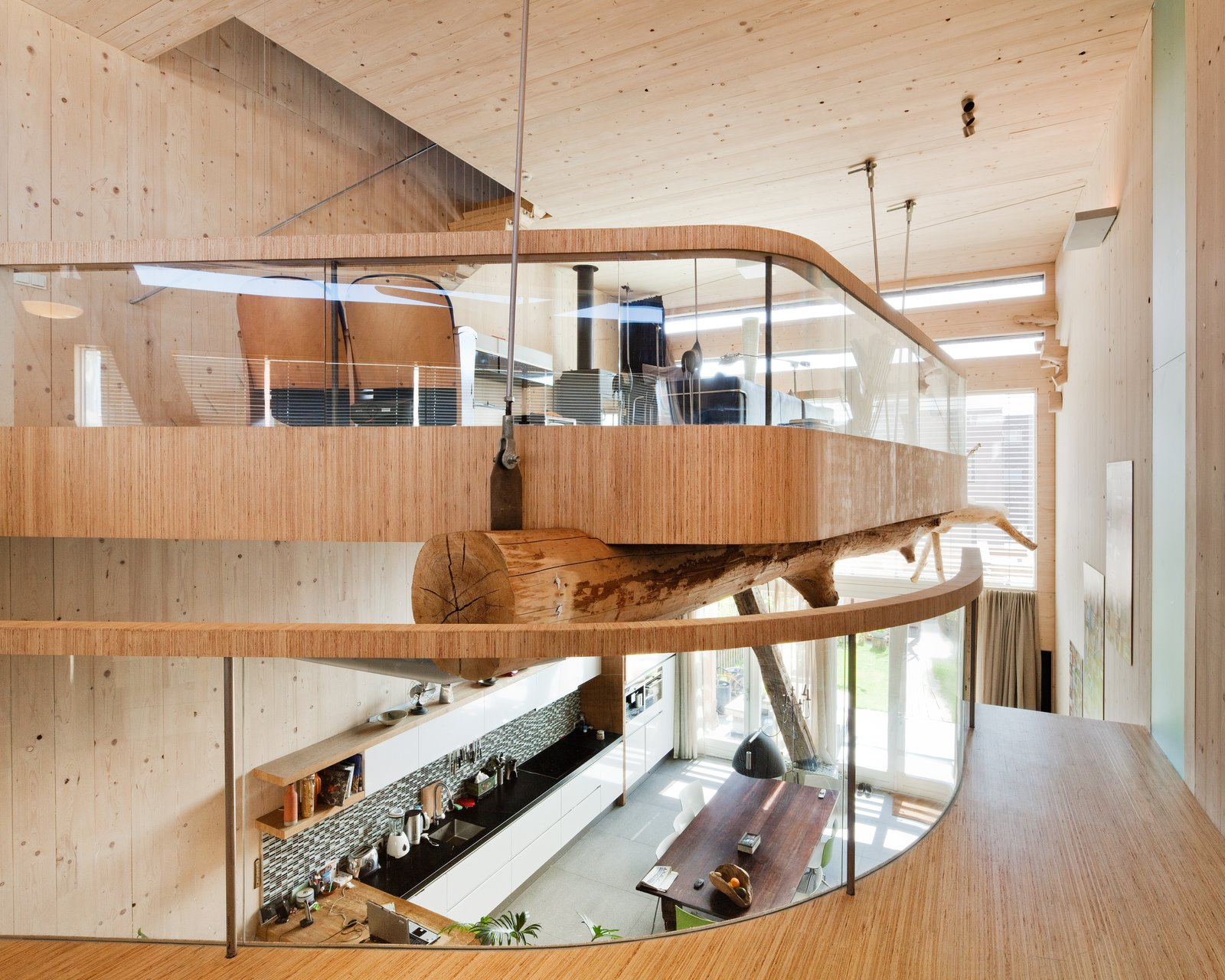 The living room is located on the split-level second floor balcony, held up by the tree trunk and secure poles. The kitchen can be seen below.  Photo 3 of 5 in A Passive House in the Netherlands Embodies 5 Tips to Consider When Planning Your Own