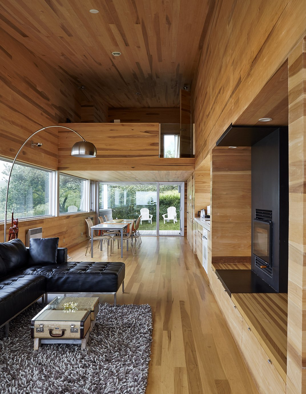 The interior of locally milled poplar contrasts with the home's metal exterior. Thanks to the six-degree pitch of the site, the dining area leads directly to the yard, while the living room ends with a balcony that's high above the ground. Tagged: Living Room, Sofa, Floor Lighting, Rug Floor, Standard Layout Fireplace, and Medium Hardwood Floor.  Photo 3 of 13 in Lights Will Guide You Home