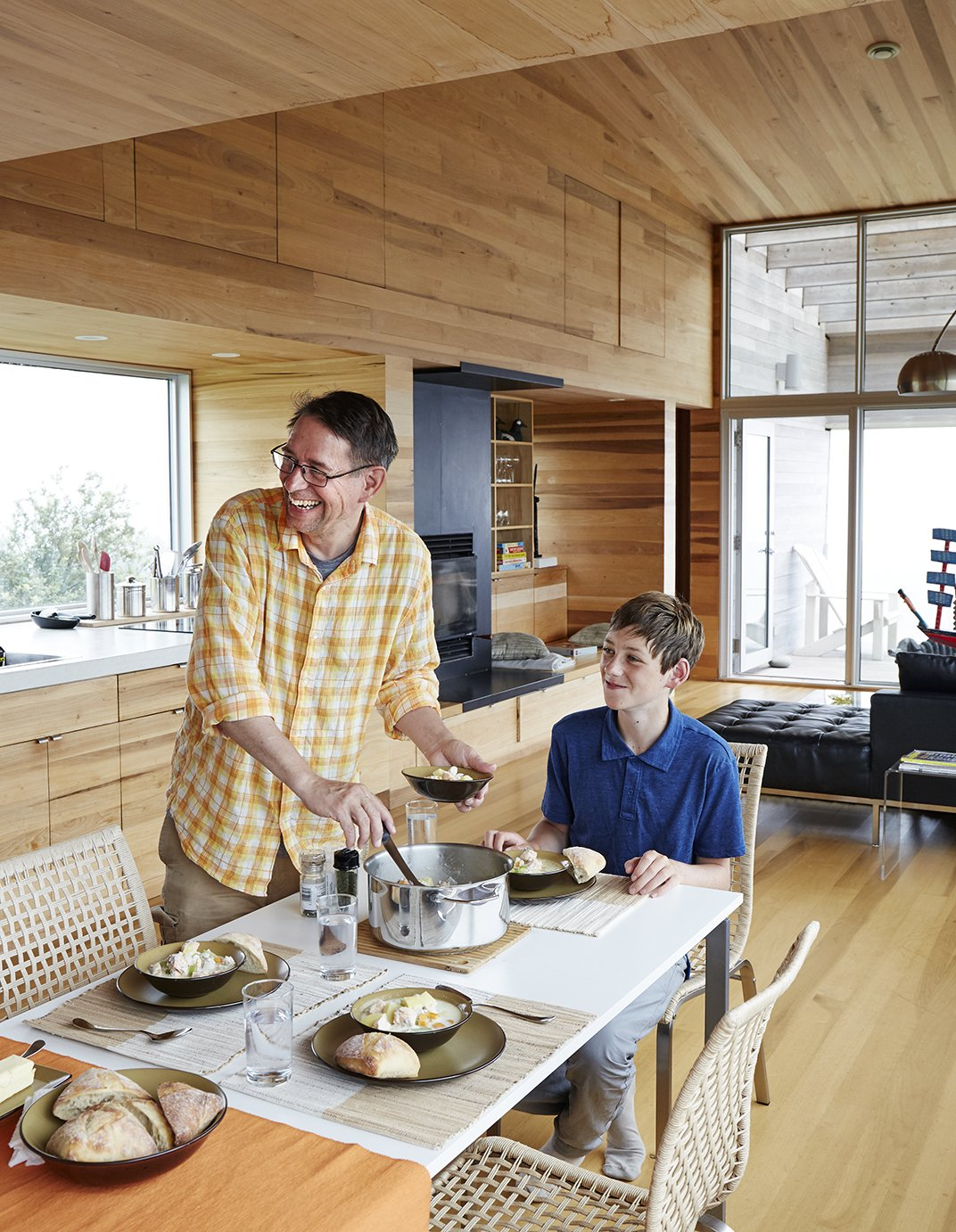 At the IKEA dining table, David Peters and his son, Dashel, enjoy a meal from a Paderno stainless-steel pot made on Prince Edward Island. Tagged: Dining Room, Table, Chair, and Light Hardwood Floor.  Photo 4 of 13 in Lights Will Guide You Home
