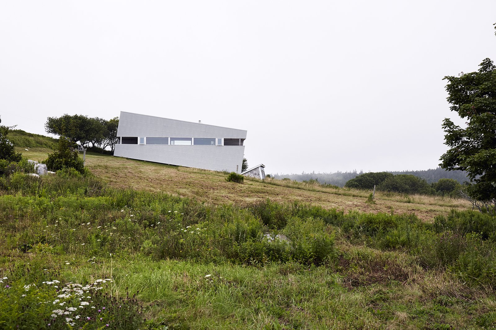 Imagined as a jewel box on a hill, Sliding House takes the place of a barn that once stood on this Nova Scotia site. Its form follows the slope of the land, while the windows are parallel with the horizon, setting up a tension between a plumb interior and a slanted exterior. The tilt of the structure isn't just a visual trick—it also helps the roof to drain. When the distinctive windows are lit from within, the house serves as a beacon for local sailors. Tagged: Side Yard, Exterior, Slope, Field, Metal Siding Material, and House.  Photo 2 of 13 in Lights Will Guide You Home