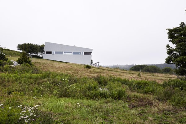 Imagined as a jewel box on a hill, Sliding House takes the place of a barn that once stood on this Nova Scotia site. Its form follows the slope of the land, while the windows are parallel with the horizon, setting up a tension between a plumb interior and a slanted exterior. The tilt of the structure isn't just a visual trick—it also helps the roof to drain. When the distinctive windows are lit from within, the house serves as a beacon for local sailors. Photo  of Sliding House modern home