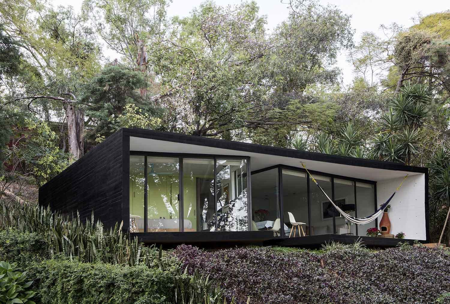 Constructed of steel, glass and concrete, the exteriors are clad in dramatic black with a floor to ceiling glass facade offering views of the valley below from the outdoor lounge area and pool.  Photo 4 of 11 in 10 Modern Vacation Homes in Mexico That Guarantee an Epic Escape