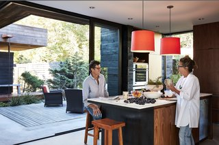 Ian Jones and Debra Peat enjoy fresh fruit grown in the backyard of their Seattle, Washington, home. Relocating from a rural community, the couple brought their passion for gardening to their new urban setting. Sliding doors from Quantum wrap around the kitchen and open to an expansive courtyard and deck, which is furnished with armchairs from Crate and Barrel. Smith pendants from Resolute hang above the PentalQuartz and marble island; the oven and dishwasher are from Miele.