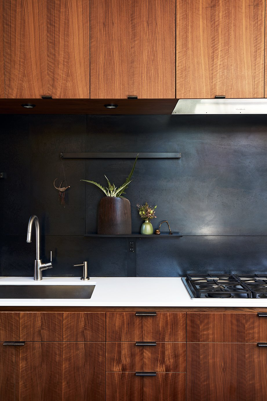 The metal backsplash and drawer pulls were fabricated by 12th Avenue Iron; the cooktop is by Miele. Tagged: Kitchen, Undermount Sink, Wood Cabinet, Metal Backsplashe, and Range.  Photo 5 of 15 in Greener Grass