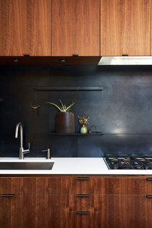 Greener Grass - Photo 4 of 14 - The metal backsplash and drawer pulls were fabricated by 12th Avenue Iron; the cooktop is by Miele.