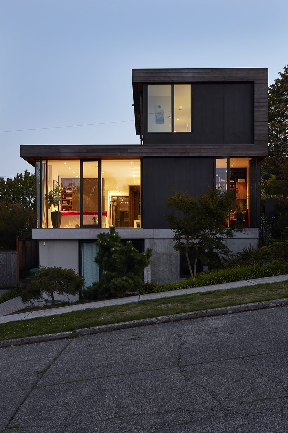 The structure is sited on a slope that dips to the east, allowing for a generous basement that Ian uses for his business, Treebird Construction. Tagged: Exterior, Wood Siding Material, Stucco Siding Material, and House.  Photo 12 of 15 in Greener Grass