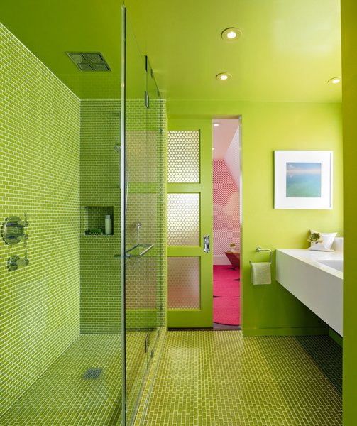 Green works its magic for Min Day in this bathroom, which contrasts with the bright pink bedroom beyond.