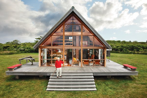 Mid-century designer Jens Risom's A-framed prefab family retreat, located on the northern portion of Block island, is bordered by a low stone wall, an aesthetic element that appears throughout the land. Photo  of Risom Residence modern home