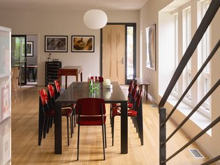 """The first floor's open plan combines kitchen, dining, and living areas; <br>rift-sawn white oak planks line the floors throughout. """"It's a tremendous enhancement of our life together,"""" Louis says of the layout. Standard chairs by Jean Prouvé for Vitra surround the beeswax-coated steel dining table."""