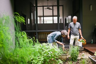 Marsha and Louis collect herbs <br>in a garden by their screened porch (above). The home's exterior cypress cladding is finished with Sikkens ProLuxe Cetol stain in Teak.