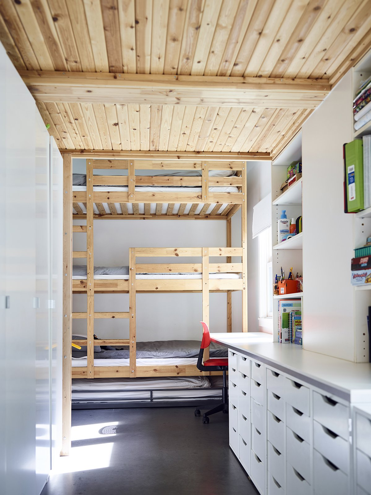 A three-level bunk bed with an additional trundle furnishes the children's room on the first floor; the cabinetry and drawers are from IKEA. Tagged: Bedroom and Bed.  Photo 6 of 11 in Across the Ocean