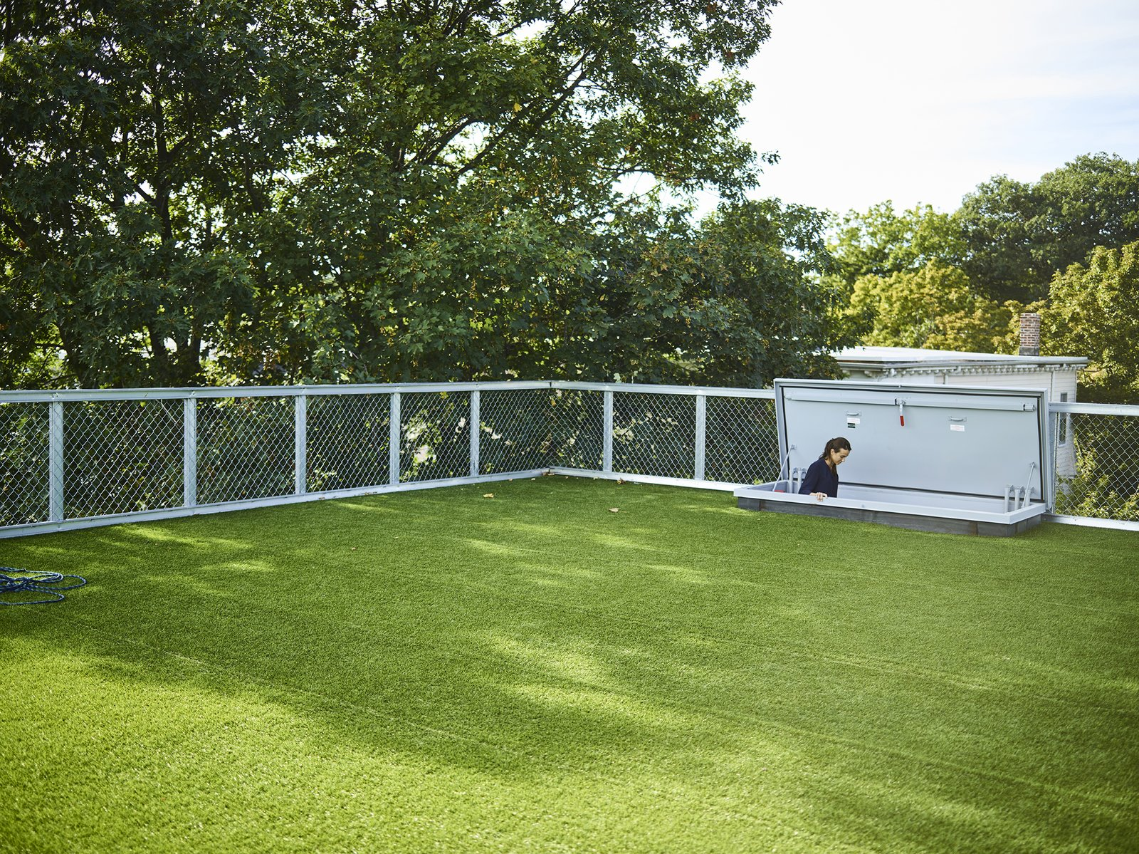 A hatch door leads to the roof deck, which is lined with artificial turf.