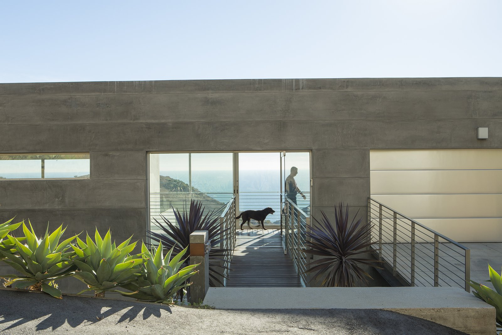 """""""Simple rectangular  volumes with simple details"""" is how designer Thomas Egidi describes the house he created for architect Carlos Dell'Acqua in Malibu. """"I wanted to stress its horizontality,"""" Dell'Acqua notes. Inside the dwelling, which is entered via a bridge that pierces the 25-foot-high main facade, the view  opens up to a panorama of mountains and sea. Ipe flooring is used for the walkway and throughout the interior."""