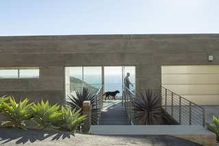 "Facing the Elements - Photo 1 of 5 - ""Simple rectangular volumes with simple details"" is how designer Thomas Egidi describes the house he created for architect Carlos Dell'Acqua in Malibu. ""I wanted to stress its horizontality,"" Dell'Acqua notes. Inside the dwelling, which is entered via a bridge that pierces the 25-foot-high main facade, the view opens up to a panorama of mountains and sea. Ipe flooring is used for the walkway and throughout the interior."