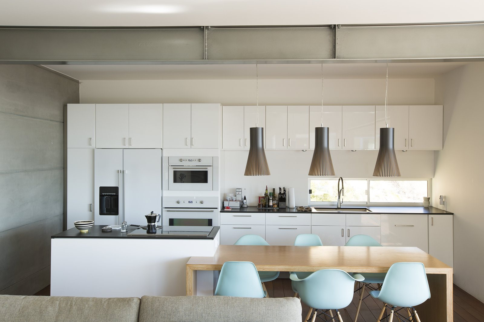 Pendants from Finnish Design Shop light a table by carpenter Leo LaPlante. The Eames chairs are from Design Within Reach.  Kitchen by Jamel from Facing the Elements